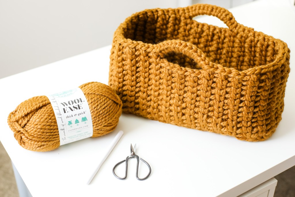 Make the Jessie Stash Basket, a chunky crochet basket, using the free pattern and included tutorial video. This easy, modern crochet storage basket is perfect for holding your projects and for gift giving. Make this large rectangle crochet yarn storage basket today! | TLYCBlog.com