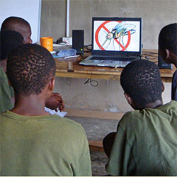 Schoolboys watch a DVD lesson teaching them how to avoid Malaria