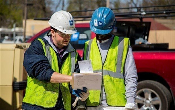 TMI Training Shows Two Men In Safety Helmets And Vests Going Over Papers.