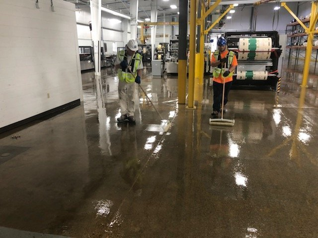 Industrial painters from TMI Coatings in the process of applying a clear floor sealer and dust proofing flooring.