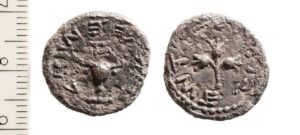"Silver Half-Shekel coin. Obverse: A chalice from the Temple topped by the letter aleph, which means ""First year"". Around it is inscribed ""Half a Shekel"". Reverse: A stem with three pomegranates surrounded by the words ""Jerusalem the Holy"".]"