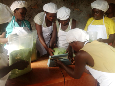 Ladies at Raintree Farms packaging moringa product for international export