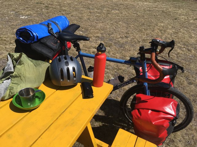 A blue bike with red panniers next to a yellow picnic table.