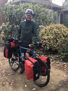 Wes Kempfer standing in drive way with bike loaded up with panniers full of gear.
