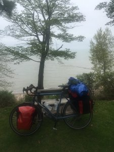 A touring bike loaded with gear, leaning on a park bench with Lake Erie in the background on a cloudy misty day.