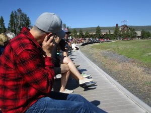 A crowd of people sitting along the deck that circle Old Faithful.