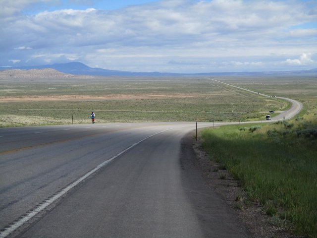 An eastbound Trans America cyclist approaches up this hill in Wyoming, north of Rawlins. There is a wide open valley at the bottom of the hill with a road crossing it. Mountains are in the distance.
