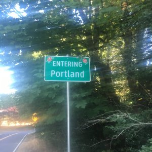 """A green road sign saying """"Entering Portland"""""""