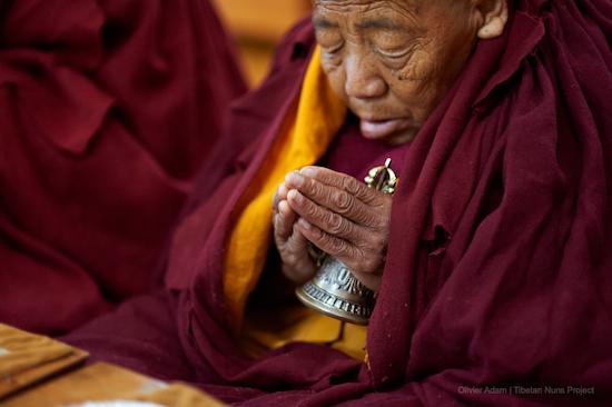 elderly Tibetan Buddhist nun holding bell