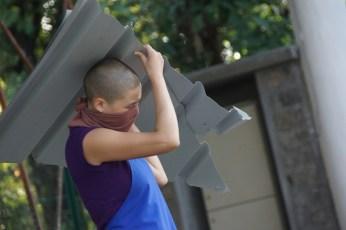 Tibetan Buddhist nun carrying metal roof piece