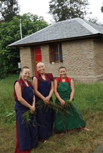 3 Tibetan Buddhist nuns in front of retreat huts