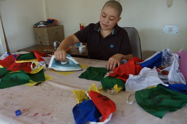 nun making Tibetan prayer flags