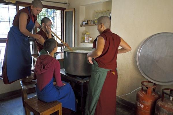 Tibetan Buddhist nuns stirring to make tofu
