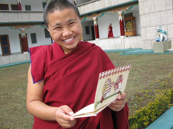 Sakya nun holding card from her sponsor 2015