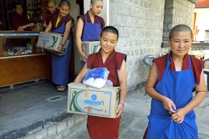 Tibetan Buddhist nuns carrying boxes