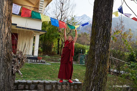 Tibetan Buddhist nun, prayer flags, hanging prayer flags