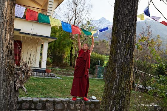 Tibetan Buddhist nun, prayer flags, hanging prayer flags