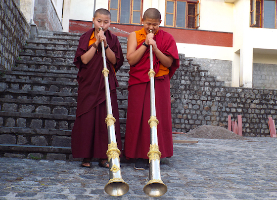Two Tibetan Buddhist nuns play the dungchen, Tibetan long horns