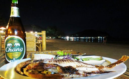 Chang beer and fish on a beach in Thailand
