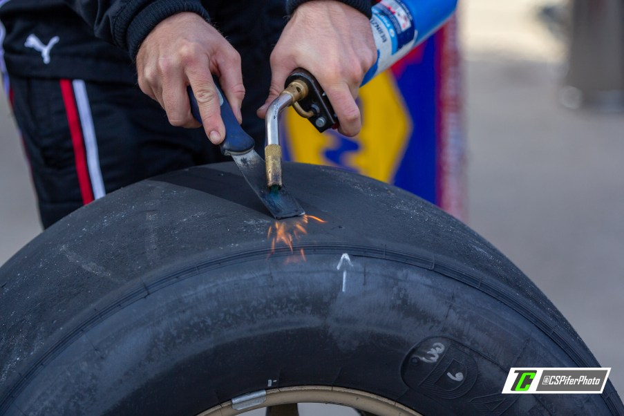 A pit crew member inspects tires after a pit stop in the AAA Texas 500. Photo Credit: Caleb Pifer / TobyChristie.com