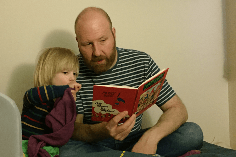 Toby and his daddy reading Noddy at bedtime