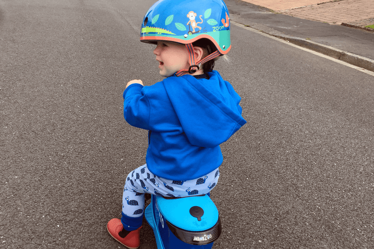 Gabe playing on his scooter in a helmet that is far too big