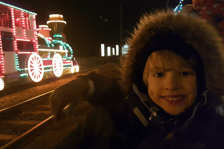 Toby at the Blackpool Illuminations with a train tram in the background