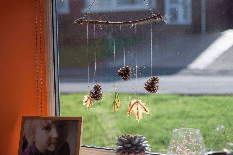 Autumn leaf and pine cone glitter decoration hanging in the window