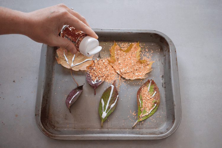 Sprinkle glitter over the glue on the leaves