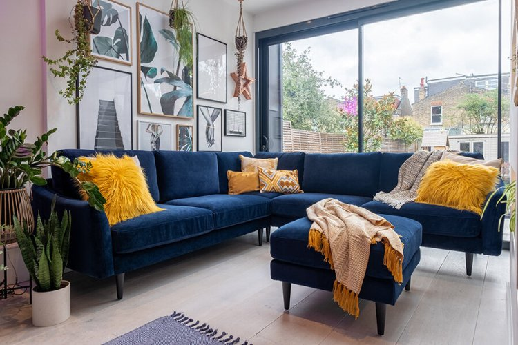 Navy velvet corner sofa with mustard yellow cushions
