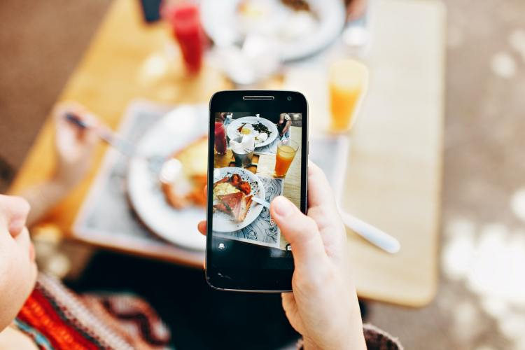 Person taking a photo of food with a mobile phone