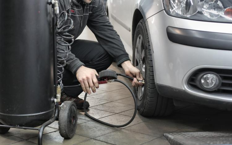 Man checking tyre pressure on a silver car