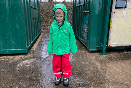 Gabe in his wet weather gear splashing in a puddle