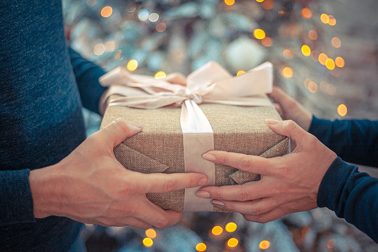 hands holding a present wrapped in brown paper with a bow on top