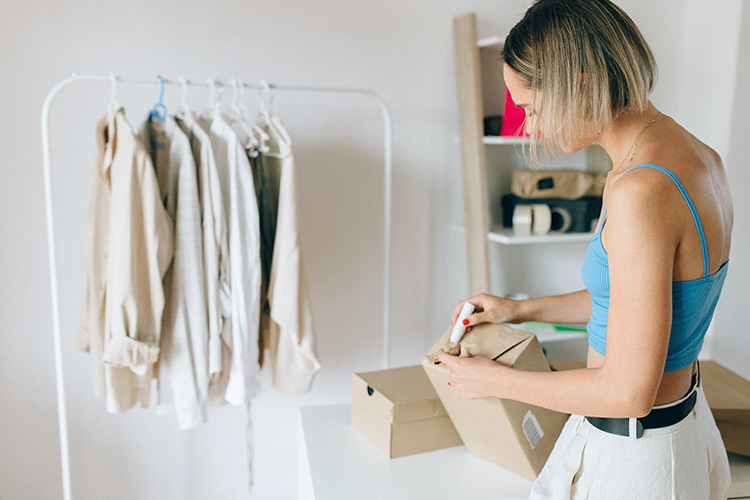 woman in blue vest top making up cardboard boxes with a rail of clothes in the background