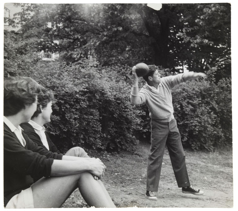 JFK in sneakers throwing a football as his sister-in-law Ethel and Jackie Kennedy spectate.