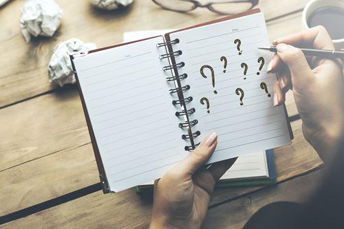 woman written question mark on notepad in office