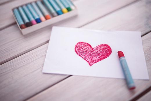 Un dibujo de un corazón rojo hecho con ceras de colores.