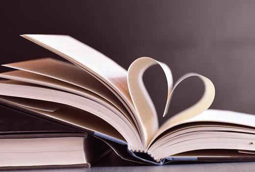 Un libro con dos hojas plegadas hacia dentro formando un corazón.