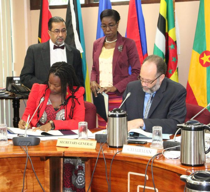 From left, UN-Women representative. Ms. Toni Brodber and CARICOM Secretary-General, Amb. Irwin LaRocque sign the MOU. Standing are Mr. Neville Bissember and Ms. Barbara Vandyke, Office of the CARICOM Secretary-General