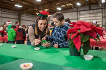 A student helps a young boy make a Christmas tree out of green pipecleaners.