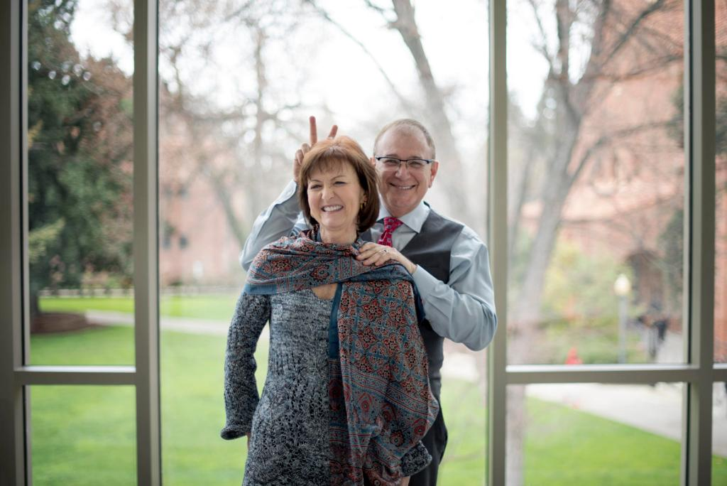 """Eddie Vela holds up """"bunny ears"""" behind Celeste Jones while standing in front of Arts Building windows that overlook campus."""
