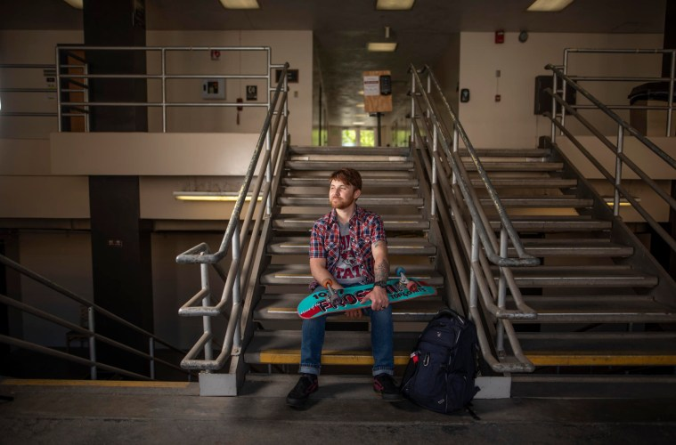 Anthony McKinney sits on a short flight of stairs holding his skateboard.