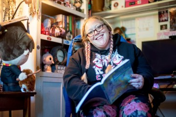 Chantel Bebee sits in a chair in her home with an open book in front of her.