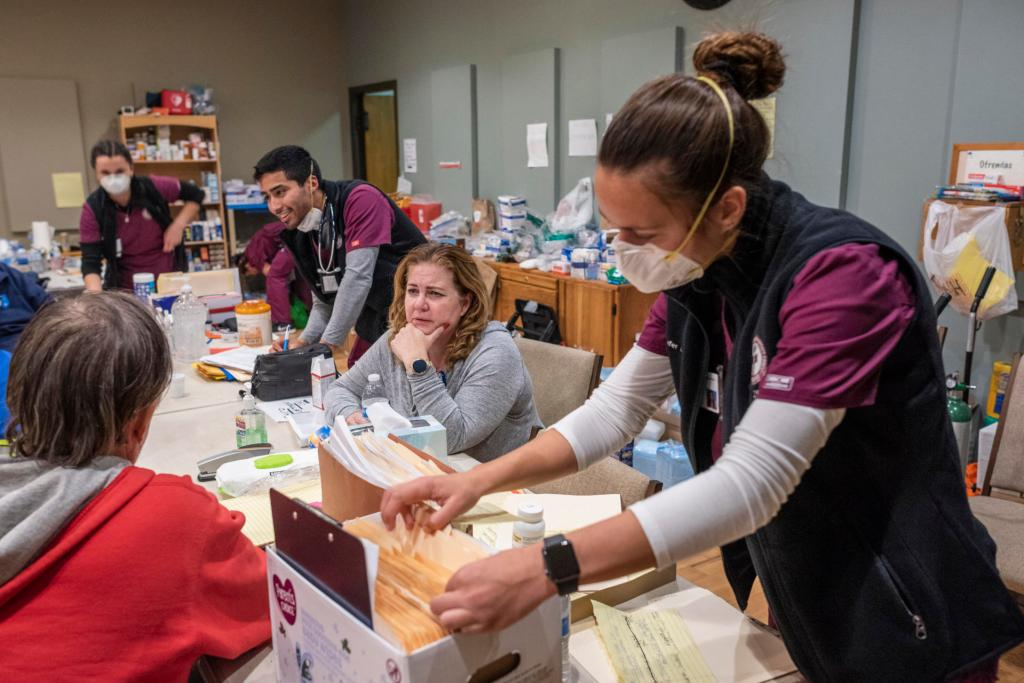 Nursing students help patients at an evacuation shelter by taking their vital information, searching through files, and offering a smile.