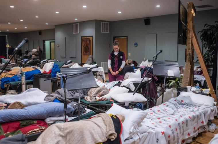 Jennifer Lefort stands among rows of beds set up at the Neighborhood Church evacuation center.
