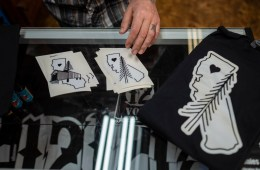 Stickers and t-shirts featuring the design of a pine tree over the state of California are displayed.