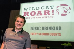 Peer Educator Evan Thibeau pictured with a powerpoint presentation on alcohol poisoning and substance abuse.