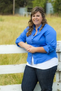 Holly Hockett posed leaning on a white picket fence at the Univesity Farm, with green pastures in the background