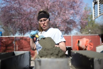 Student in safety glasses shovels concrete into a mold